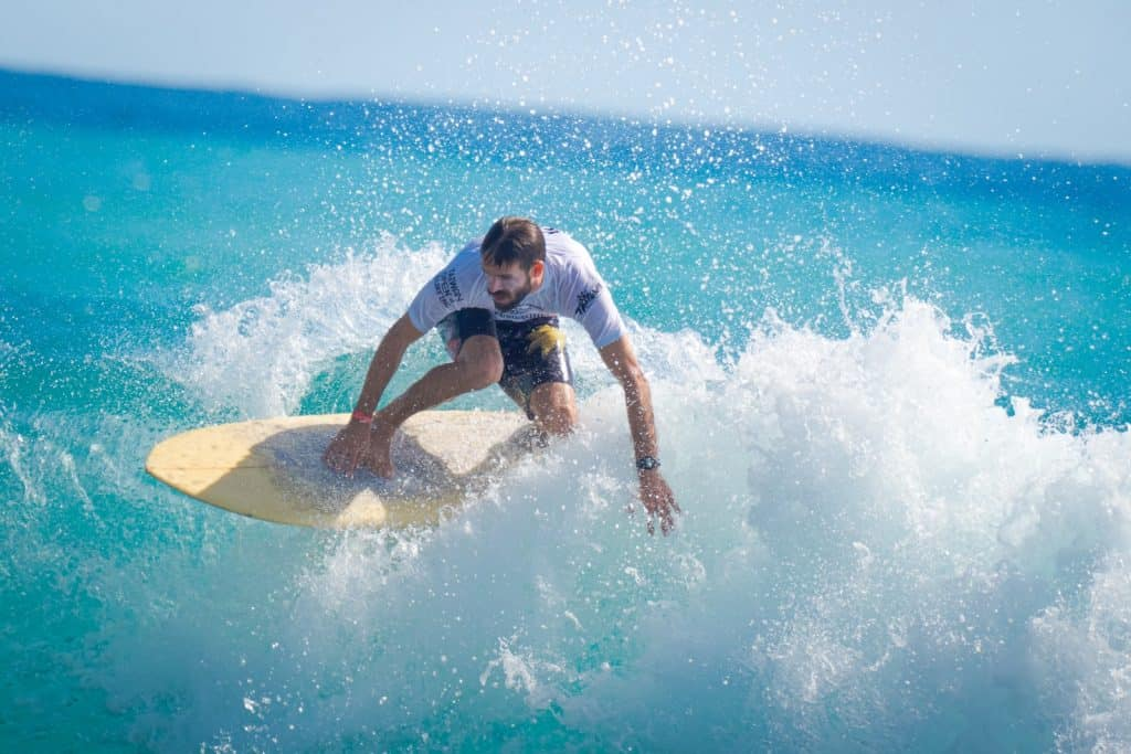 man in white t-shirt and blue shorts surfing on sea waves during daytime